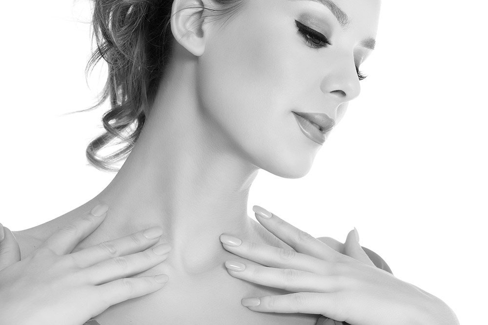 Woman touching her collarbones, looking downt to the side